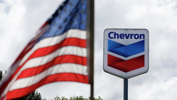 FILE - In this May 23, 2013, file photo, a United States flag flies in view of a Chevron gas station in Blaine, Wash. Chevron reports quarterly earnings on Friday, Jan. 31, 2014. - Sputnik Mundo