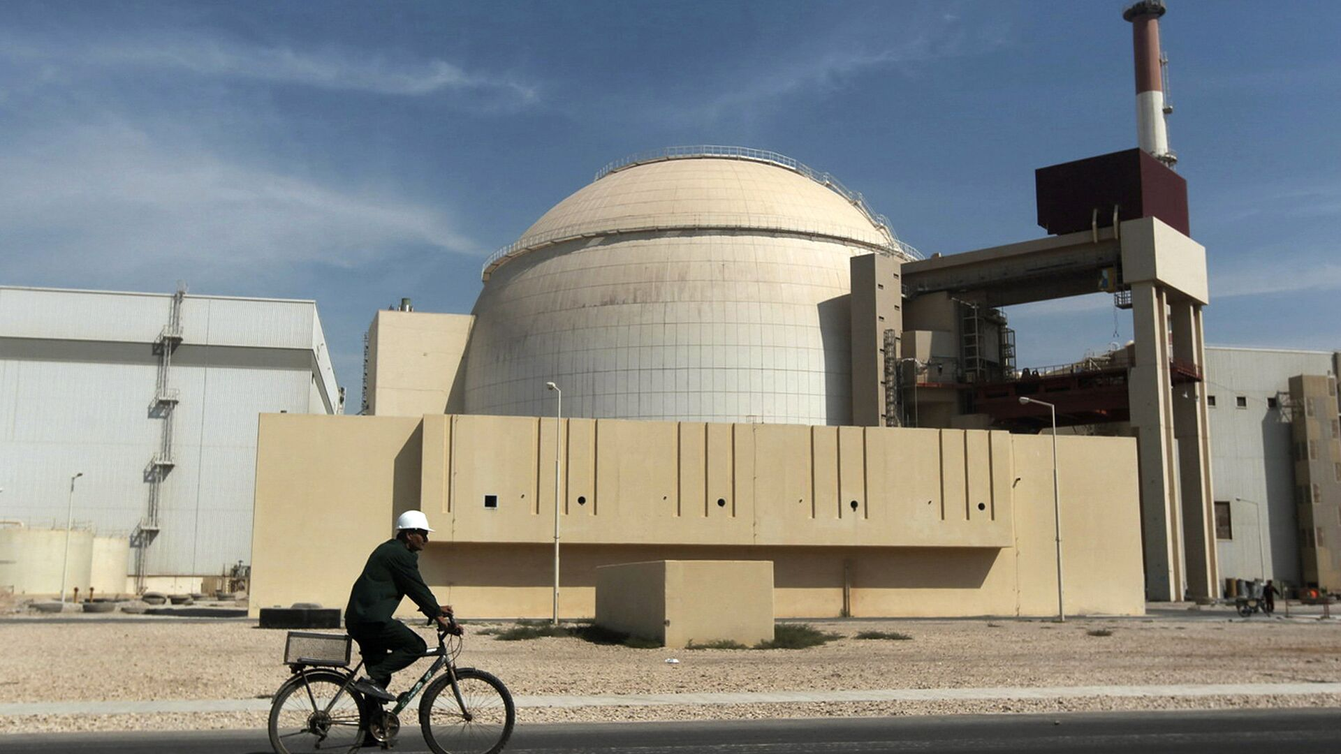 In this Oct. 26, 2010 file photo, a worker rides a bicycle in front of the reactor building of the Bushehr nuclear power plant, just outside the southern city of Bushehr. - Sputnik Mundo, 1920, 01.04.2021