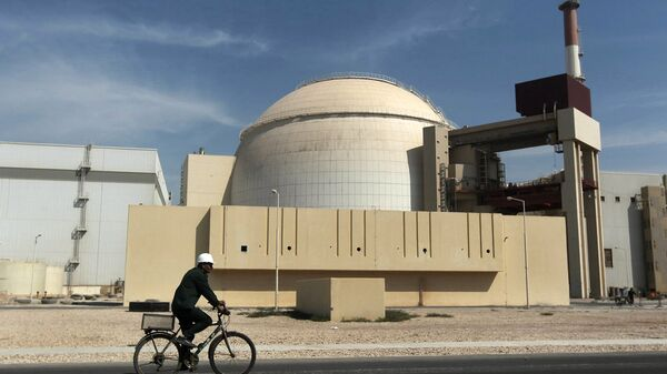 In this Oct. 26, 2010 file photo, a worker rides a bicycle in front of the reactor building of the Bushehr nuclear power plant, just outside the southern city of Bushehr. - Sputnik Mundo