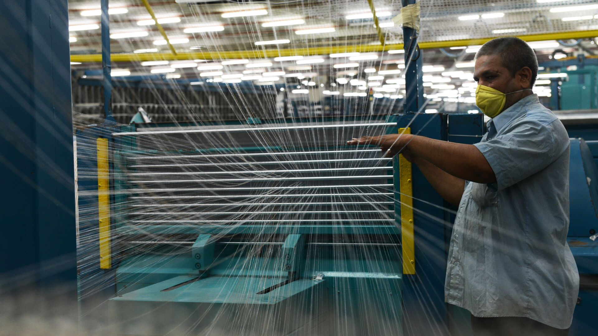 In this photograph taken on July 8, 2014 an Indian employee works at a textile factory in Khatraj village, some 20 kms from Ahmedabad. - Sputnik Mundo, 1920, 16.06.2021