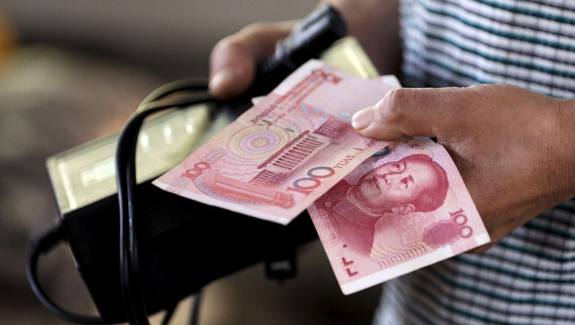 A customer holds a 100 Yuan note at a market in Beijing, August 12, 2015 - Sputnik Mundo, 1920, 22.11.2020