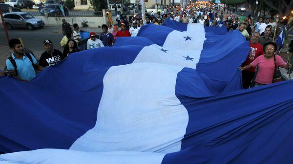 Manifestantes con la bandera de Honduras - Sputnik Mundo
