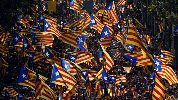 A file picture taken on September 11, 2014 shows demonstrators waving Estelada flags (Catalan independentist flags) during celebrations of the Diada (Catalonia National Day) in Barcelona.  - Sputnik Mundo