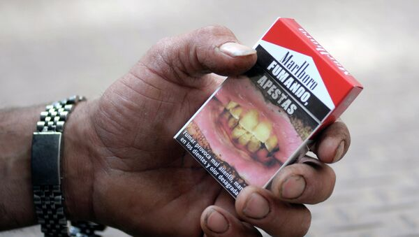 Cajetilla de cigarrillos con una advertencia 'Fumando, apestas' - Sputnik Mundo