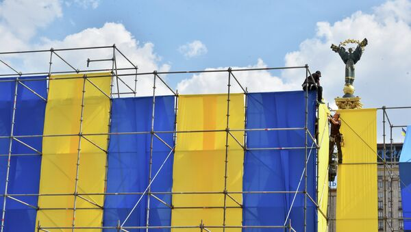 Workers decorate Independece Square with Ukrainian flags during National Flag Day celebrations in Kiev on August 23, 2015. - Sputnik Mundo