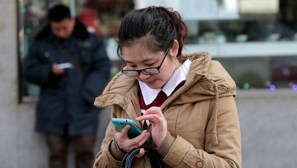 Los chinos comprueban sus teléfonos en una calle de Beijing - Sputnik Mundo