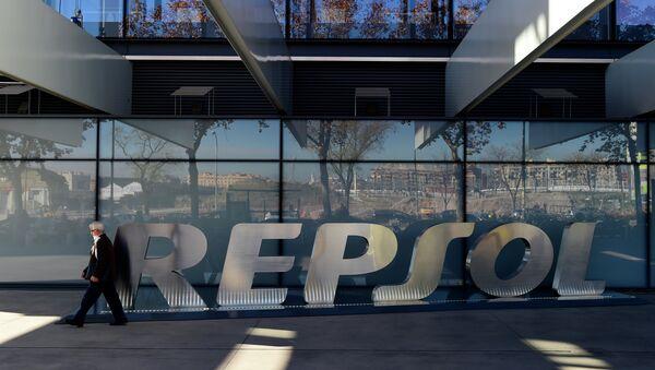 A woman walks past the headquarters of Spanish oil company Repsol in Madrid on December 16, 2014 - Sputnik Mundo