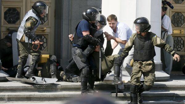 Militares ucranianos llevan un herido durante enfrentamientos junto a la sede del Parlamento ucraniano - Sputnik Mundo