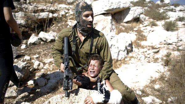Un soldado israelí detiene a un niño palestino durante una protesta en la aldea cisjordana de Nabi Saleh - Sputnik Mundo