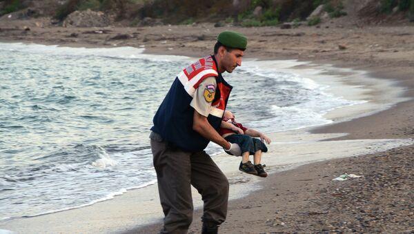Un oficial de la policía paramilitar lleva el cuerpo sin vida de Aylan Kurdi - Sputnik Mundo