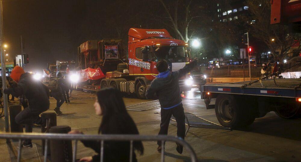 Activista de la comunidad mapuche lanza una piedra a un camión en Santiago