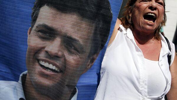 Participante de las manifestaciones con un retrato de Leopoldo López - Sputnik Mundo