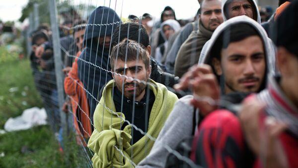 Refugiados esperan en una cola para subir a un autobús en Hegyeshalom, Hungría - Sputnik Mundo
