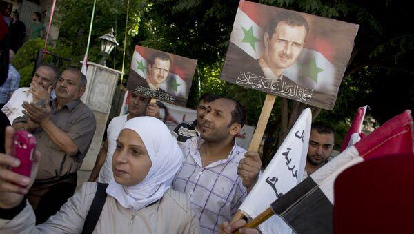 La gente tiene retratos del presidente sirio Bashar Assad fuera de un centro de votación en Damasco - Sputnik Mundo