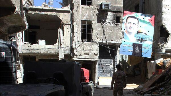 Un retrato del presidente sirio Bashar al-Assad en una calle de la capital siria, Damasco, el 6 de abril de 2015 - Sputnik Mundo