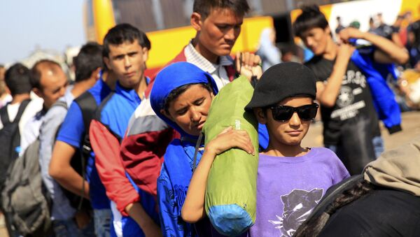 Los inmigrantes suben a un autobús después de cruzar la frontera de Serbia cerca Röszke, Hungría - Sputnik Mundo