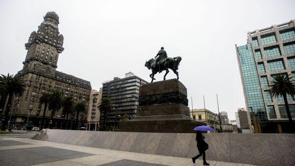 Una persona camina en la vacía Plaza de la Independencia en el centro de Montevideo durante una huelga de 24 horas en reclamo de aumentos salariales - Sputnik Mundo