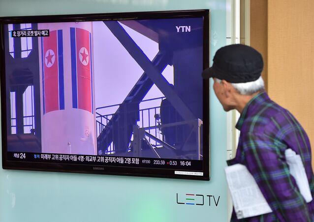 Un anciano ve las noticias sobre las reparaciones para el lanzamiento de un cohete norcoreano