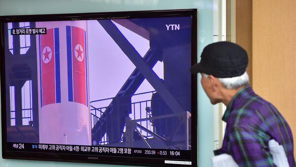 Un anciano ve las noticias sobre las reparaciones para el lanzamiento de un cohete norcoreano - Sputnik Mundo
