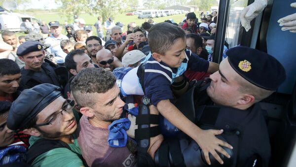 Policía croata ayuda a un niño de refugiado a subirse al autobús en Tovarnik, Croacia - Sputnik Mundo