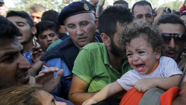 Refugiado abraza a una niña al esperar en la cola para subirse al autobús en Tovarnik, Croacia - Sputnik Mundo