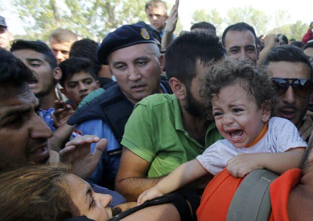 Refugiado abraza a una niña al esperar en la cola para subirse al autobús en Tovarnik, Croacia