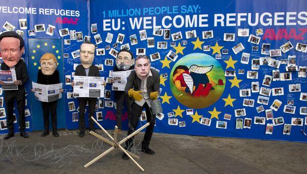 Actores disfrazados de David Cameron, Angela Merkel, Francois Hollande, Mariano Rajoy y Viktor Orbán cerca del retrato de Aylan Kurdi - Sputnik Mundo