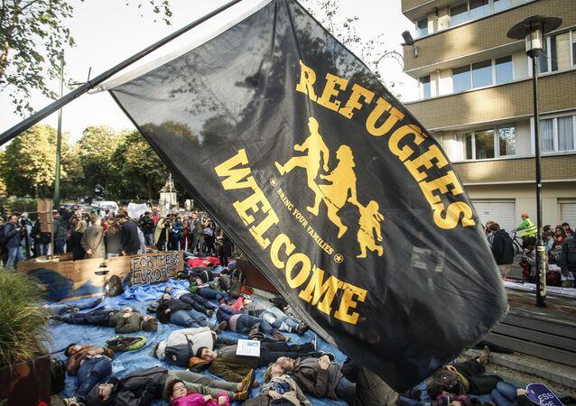 Protestantes en Bruselas con la bandera 'Bienvenido, refugiados'