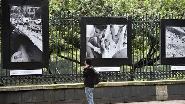Un pasador mira a las fotos que demuestran las consecuencias del terremoto de 1985 en México - Sputnik Mundo