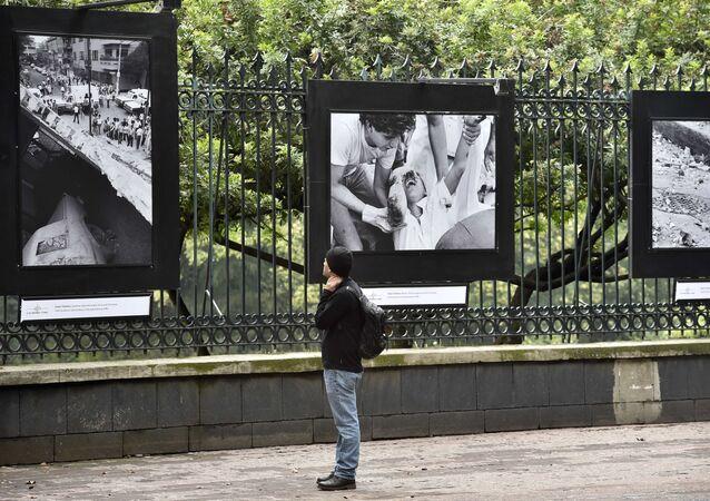 Un pasador mira a las fotos que demuestran las consecuencias del terremoto de 1985 en México