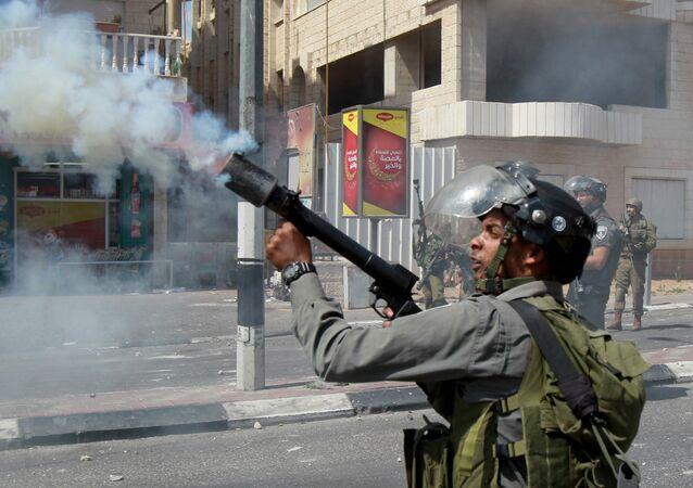 Guardafronteras de Israel tira el gas lacrimógeno durante el choque armado con los jóvenes palestinos