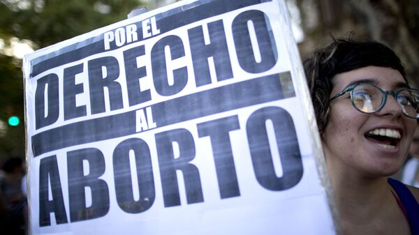 A woman holds a banner that reads in Spanish For the right to abort, during a rally in Buenos Aires, Argentina - Sputnik Mundo