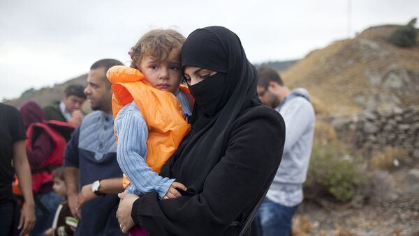 A Syrian refugee holds a child following their arrival on the Greek island of Lesbos after crossing a part of the Aegean Sea from the Turkish coast, September 29, 2015. - Sputnik Mundo