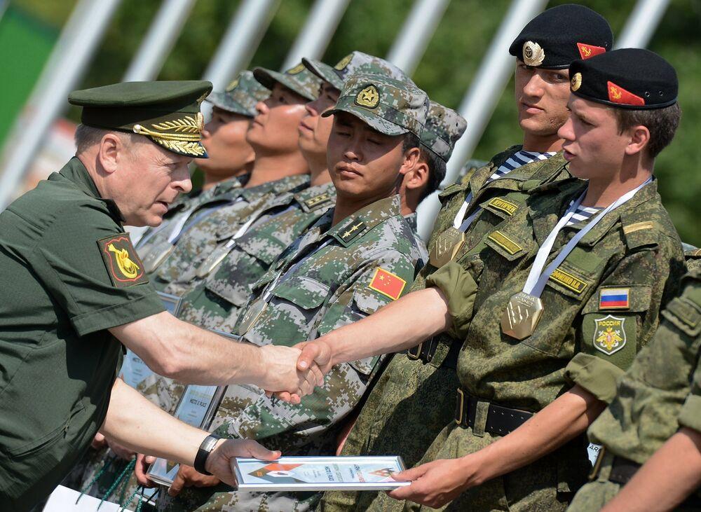 El comandante de las fuerzas terrestres de Rusia, coronel general Oleg Saliukov (izquierda) otorga premios a la tripulación de carro de combate que ganó en los Juegos Militares Internacionales 2015 (JMI 2015)