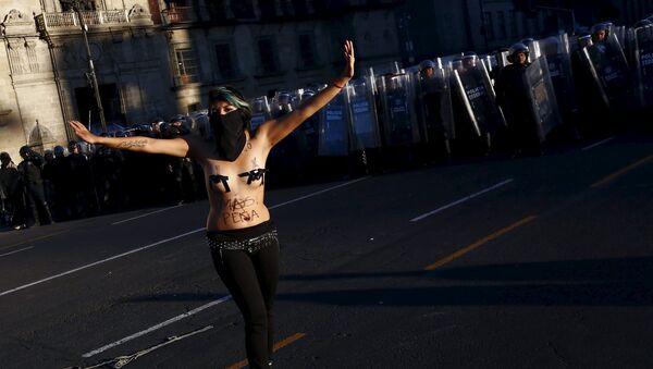 Una manifestante hace gestos frente a la policía antidisturbios durante los enfrentamientos con la policía antidisturbios en una marcha por el aniversario de la masacre de la plaza Tlatelolco en 1968 - Sputnik Mundo