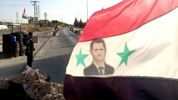 Bandera con una imagen de Bashar Asad - Sputnik Mundo
