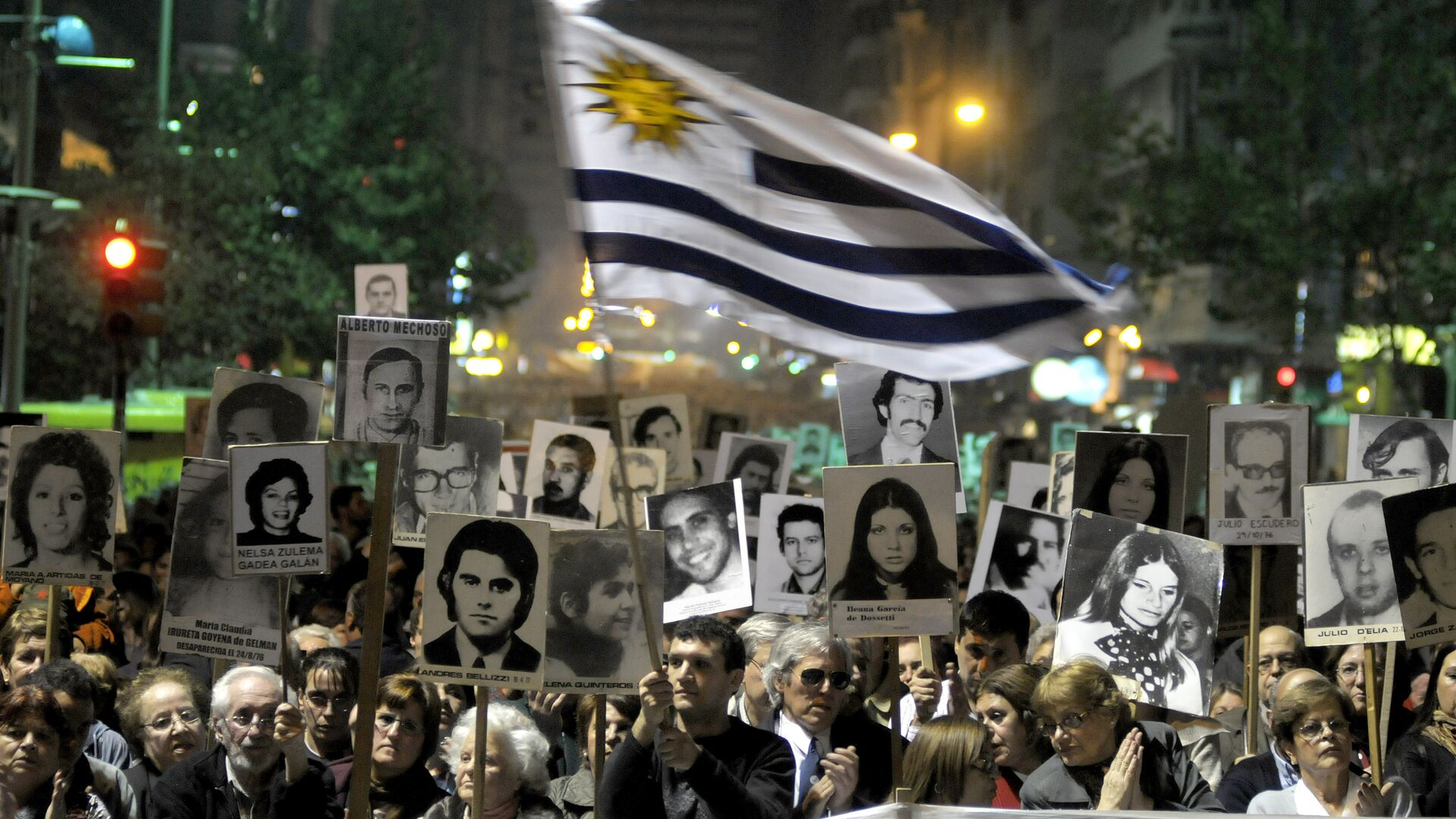 Demonstrators, one waving an Uruguayan flag, carry signs with images of people missing during Uruguay's 1973-85 dictatorship during a march in Montevideo, Uruguay - Sputnik Mundo, 1920, 11.05.2021