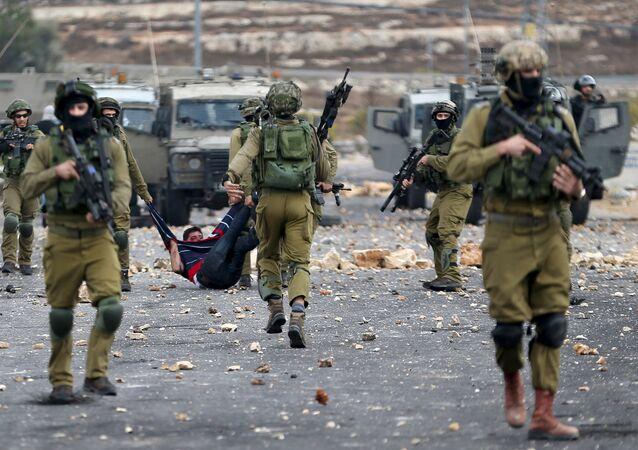 Soldados israelíes detienen un protestante palestino