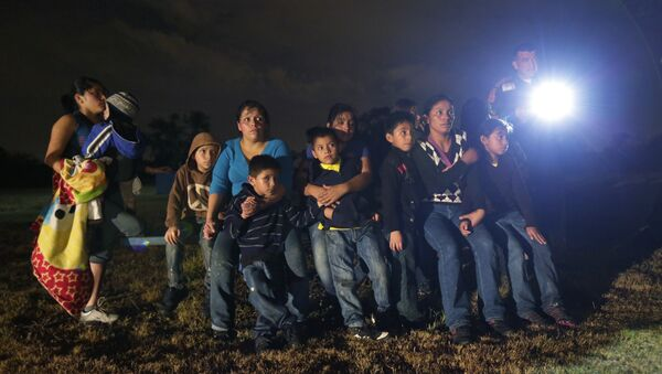 A group of young migrants from Honduras and El Salvador who crossed the U.S.-Mexico border illegally as they are stopped in Granjeno, Texas - Sputnik Mundo