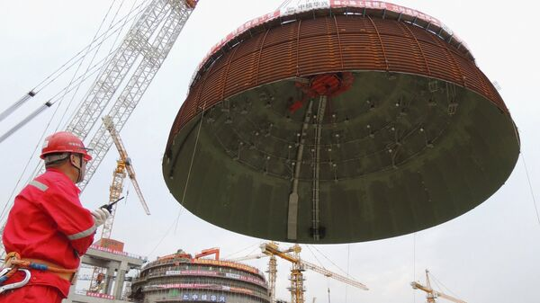 A worker looks on as the dome roof of a generator unit is lifted to be installed, at Tianwan Nuclear Power Plant, in Lianyungang, Jiangsu province, China, September 26, 2015. - Sputnik Mundo