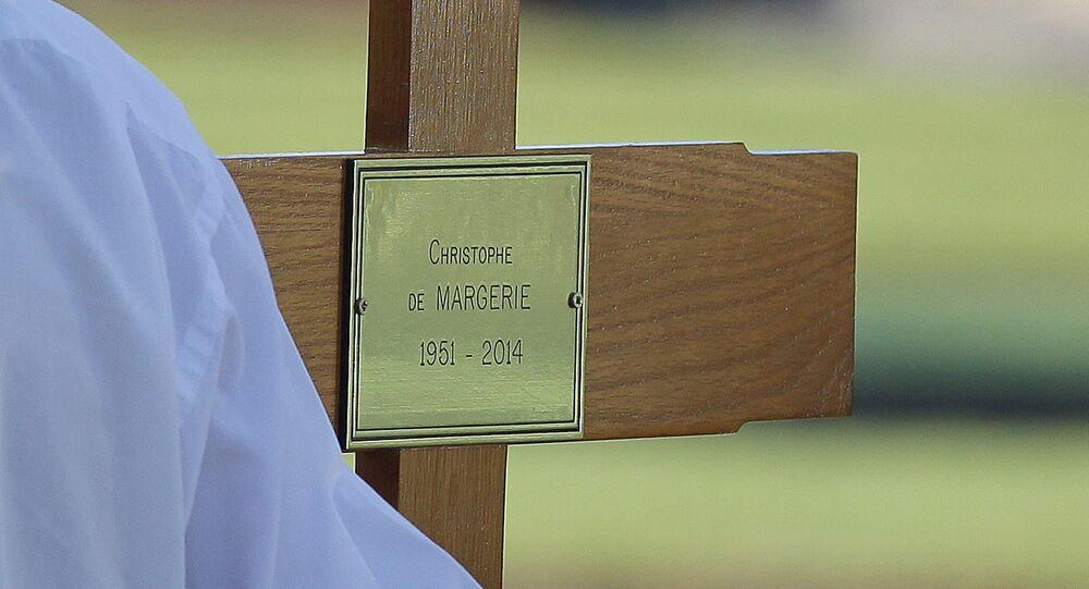 Un hombre con una cruz con el nombre de Christophe de Margerie, el presidente de la petrolera francesa Total