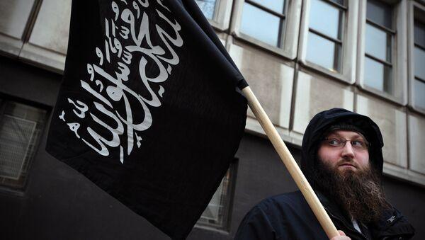 Manifestante con una bandera musulmána en Londres - Sputnik Mundo