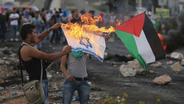 Manifestante palestino quema una bandera israelí - Sputnik Mundo