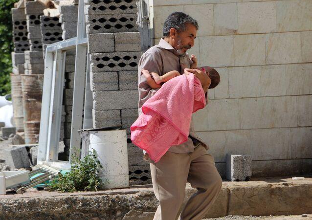 Un hombre lleva a su hija herida al hospital en la ciudad yemení de Taiz