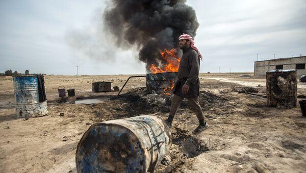 Un hombre trabaja en una refinería de petróleo improvisada en Raqqa - Sputnik Mundo