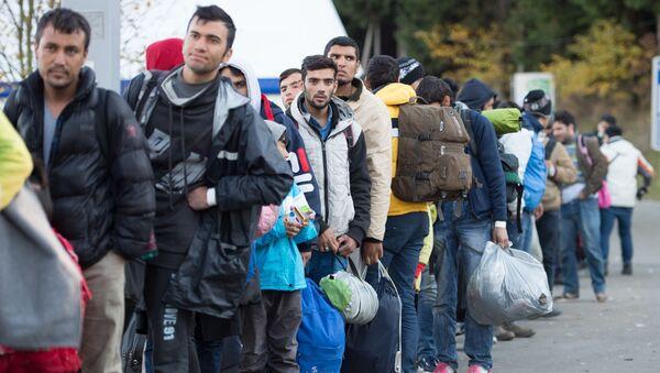 Refugiados esperan en la cola tras cruzar la frontera entre Alemania y Austria - Sputnik Mundo