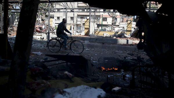 Un hombre en bicicleta en Douma, un barrio a las afueras de Damasco - Sputnik Mundo