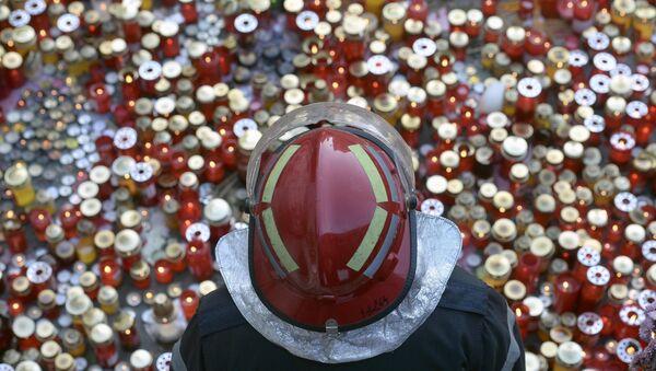 Bombero se encuentra junto a un monumento que conmemora a las víctimas de un incendio en Bucarest - Sputnik Mundo