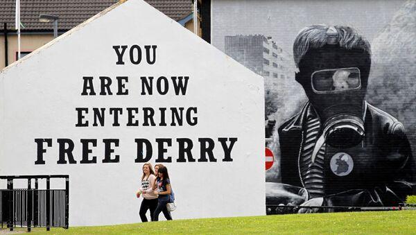 Niñas pasan junto a un mural 'Domingo Sangriento' en el área de Bogside de Londonderry, Irlanda del Norte - Sputnik Mundo