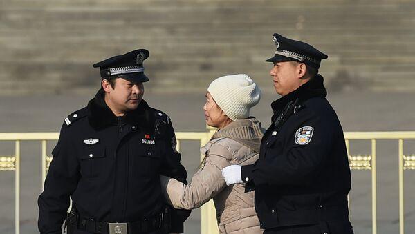 Policías chinos detienen a una mujer en Pekín - Sputnik Mundo
